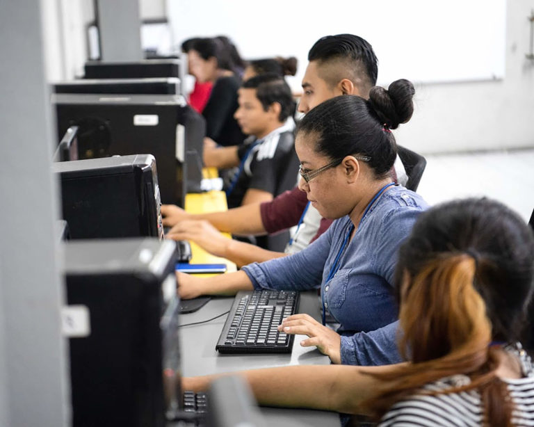 Adult students at desktops learning